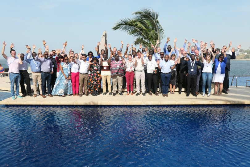 Group picture of MPRU conference delegates. Picture shows around 53 people of various ages, genders and ethnicity standing in front of a pool, with one hand raised. A palm tree, half hidden sculpture and clear skies are in the background.