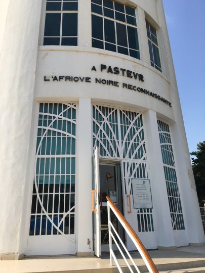 """Picture of the entrance of Institut Pasteur de Dakar (IPD), a white building with many windows, an open glass door and handrail from the steps leading to the entrance. Building sign  reads """"A PASTEVR, L'AFRIOVE NOIRE RECONNAISSANTE"""""""