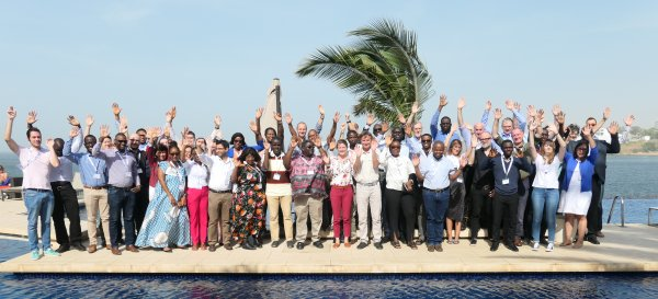 A diverse group of scientists with their arms raised standing next to a swimming pool and the sea in Dakar, 2019